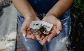 hands holding coins and a note that states